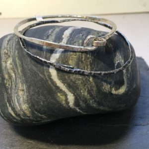 Sterling silver forged bangle, twisted and hammered with an fixed overlap or knot finish. Designed and hand made by Carol James of Silverfish Designs