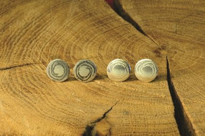 Small silver disc studs inspired by prehistoric carvings at Barclodiad y Gawres, Anglesey, handmade by Carol James of Silverfish Designs