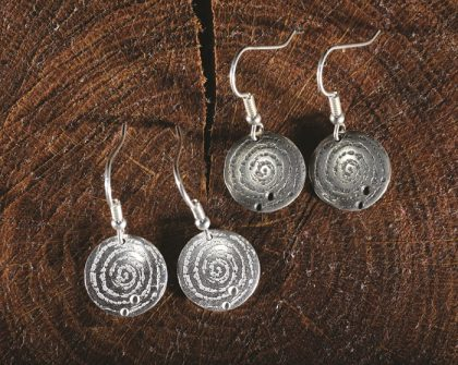 Silver disc drop earrings inspired by prehistoric carvings from the Llanbedr Spiral Stone, North Wales. Designed and created by Carol James of Silverfish Designs