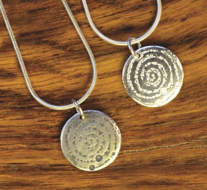 A small silver pendant inspired by the prehistoric carved stone in Llanbedr. Designed and created by Carol James of Silverfish Designs