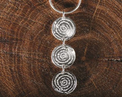 Llanbedr spiral triple pendant, inspired by prehistoric carving on the Llanbedr stone and created by Carol James of Silverfish Designs