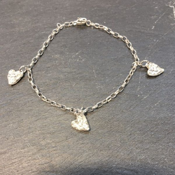 Sterling silver link bracelet with 3 tiny solid silver hearts, reticulated to give a lovely textural finish. Silver jewellery designed and handmade by Carol James of Silverfish Designs.