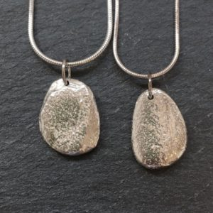 Sterling silver pendant cast from natural beach pebbles from Anglesey. Designed and hand made by Carol James of Silverfish Designs