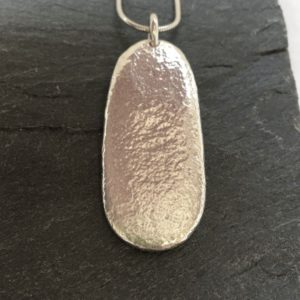 Stunning sterling silver pebble cast from a natural beach pebble from Anglesey. Designed and hand made by Carol James of Silverfish Designs